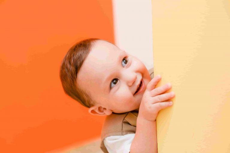 Çocuklarda Dikkat Eksikliği ve Hiperaktivite Bozukluğu başlıklı yazıda kullanılan, duvarın arkasından gülümseyen bebek