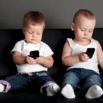 Teknolojinin Çocuk Gelişimine Etkisi başlıklı makalede kullanılan, cep telefonuyla oynayan iki çocuğun bir koltukta otururken çekilmiş fotoğrafı